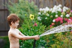 Roześmiany chłopiec podlewanie kwitnie od ogrodowego węża elastycznego Zdjęcia Stock
