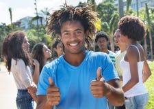 Roześmiany kolumbijski facet pokazuje kciuki z przyjaciółmi Zdjęcia Stock