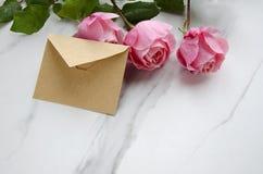 Rozen en een ambachtenvelop als symbool van valentijnskaartendag stock foto's