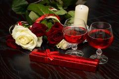 Rozen, glazen van wijn en een doos met een juweel in het licht van kaarsen Stock Afbeeldingen