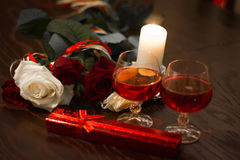 Rozen, glazen van wijn en een doos met een juweel in het licht van kaarsen Stock Foto's
