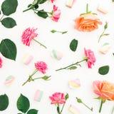 Rozen, knoppen, bladeren en heemst met suikergoed op witte achtergrond Vlak leg, hoogste mening De achtergrond van de lente Stock Foto's