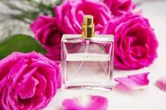 Rozenparfum in transparante fles met roze rozen en bloemblaadjes stock afbeeldingen