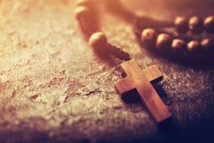 Rozentuin met houten kruis op steenachtergrond stock foto's