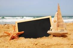 Rozgwiazda, żaglówka i chalkboard, na dennym piasku i oceanu horyzoncie Zdjęcia Stock