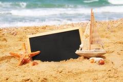 Rozgwiazda, żaglówka i chalkboard, na dennym piasku i oceanu horyzoncie Obrazy Stock