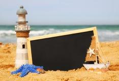 Rozgwiazda, żaglówka, latarnia morska i chalkboard, na dennym piasku i oceanu horyzoncie Zdjęcie Stock