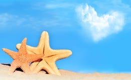 Rozgwiazdy na serce chmurze i plaży zdjęcia stock