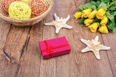 Rozgwiazdy, prezent i róże na drewnianym stole, Zdjęcia Stock
