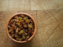 Rozijnen, in een bruine kleiplaat op de lijst stock foto