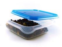 Rozijnen, Sultanarozijnen en Gedroogd fruit in Tupperware Stock Foto's