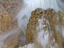 Rozjaśnia, leje się wodnego pluśnięcia puszek nad kamieniami Zdjęcia Stock