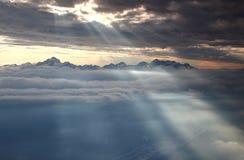 Rozjarzeni słońce promienie iluminują śnieżnych Juliańskich Alps i morze chmury Obraz Royalty Free