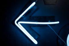 Rozjarzona błękitna neonowa strzała na czerni ścianie Olśniewający skutka znak pokazuje sposób opuszczać Zdjęcia Royalty Free