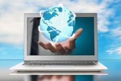 Rozjarzona orbity kula ziemska w ręce przez laptopu Obraz Royalty Free