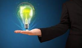 Rozjarzony lightbulb w ręce biznesmen Obrazy Royalty Free