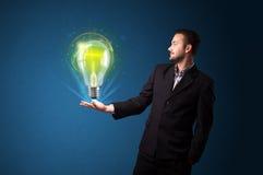 Rozjarzony lightbulb w ręce biznesmen Obraz Stock