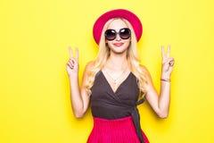 Rozkrzyczana młoda kobieta mruga pokoju znaka i pokazuje dwa palec w eleganckiej pasiastej sukni lub zdjęcia royalty free
