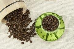 Rozlewać kawowe fasole, kawowy kubek Obrazy Royalty Free