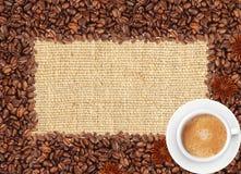 Rozlewająca kawowych fasoli rama nad burlap filiżanką i tkaniną Obrazy Royalty Free