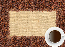 Rozlewająca kawowych fasoli rama nad burlap kawą i tkaniną Zdjęcia Stock