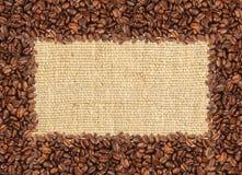 Rozlewająca kawowych fasoli rama nad burlap tkaniną Zdjęcia Stock