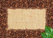 Rozlewająca kawowych fasoli rama nad burlap tkaniną Zdjęcia Royalty Free