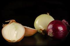 Rozmaitość cebule na czarnym drewnianym tle Obrazy Royalty Free