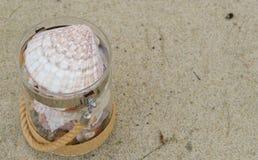 Rozmaitość denne skorupy w szklanym słoju na piasek plaży z kopii przestrzenią Wakacyjny poj?cie fotografia stock