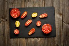 Rozmaitość dojrzałych świeżych organicznie ogrodnictwo pomidorów różny rodzaj i kolory z liśćmi w drewnianej tacy wodnego punktu  obrazy royalty free