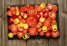 Rozmaitość dojrzałych świeżych organicznie ogrodnictwo pomidorów różny rodzaj i kolory z liśćmi w drewnianej tacy wodnego punktu  fotografia stock