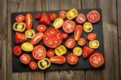 Rozmaitość dojrzałych świeżych organicznie ogrodnictwo pomidorów różny rodzaj i kolory z liśćmi w drewnianej tacy wodnego punktu  fotografia royalty free