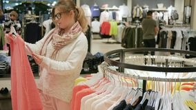 Rozmaitość kolorowi ubrania wiesza na drewnianych wieszakach w sklepie, Szczęśliwy żeński shopaholic kupuje suknię, cajgi, bluzka zbiory