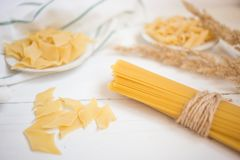 rozmaitość makaron na białym drewnianym stole, spaghetti, Penne, maltagliati, lokalna kuchnia zdjęcia stock