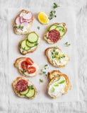 Rozmaitość mini kanapki z kremowym serem, warzywami i salami, Kanapki z serem, ogórek, rzodkiew, pomidory, salami, t Fotografia Royalty Free
