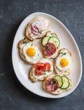 Rozmaitość mini kanapki z kremowym serem, warzywami, przepiórek jajkami i salami, Kanapki z serem, ogórek, rzodkiew, tomatoe Zdjęcie Royalty Free