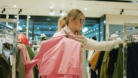 Rozmaitość rzeczy wiesza na wieszakach w odzież sklepie, Kolorowe suknie w rękach szczęśliwa blondynka, Szalony dziewczyny robić zbiory wideo