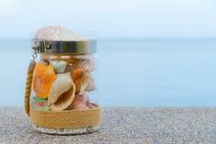 Rozmaito?? denne skorupy w szklanym s?oju i seascape na tle z kopii przestrzeni? Wakacyjny poj?cie zdjęcie stock