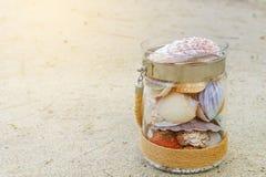 Rozmaito?? denne skorupy w szklanym s?oju na piasek pla?y z kopii przestrzeni? Wakacyjny poj?cie zdjęcia royalty free