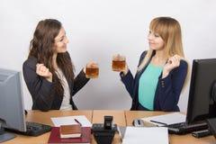 Rozmowa nad herbatą dwa biurowego pracownika przy biurkiem Zdjęcia Stock