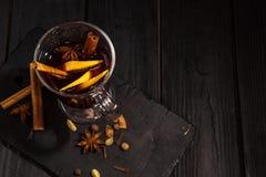 Rozmyślający wino na czarnym drewnianym stole, cynamonowych kijach i pomarańcze, odgórny widok zdjęcia royalty free