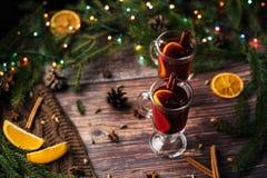 Rozmyślający wino w dwa szkłach z cynamonem, gwiazdowym anyżem, kardamonem, cloves i pomarańcze plasterkami na drewnianym stole, fotografia royalty free