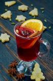Rozmyślający wino z pomarańczowymi plasterka i zimy pikantność - cynamonu, kardamonu i anyżu gwiazdy na czarnym drewnianym tle, zdjęcia stock