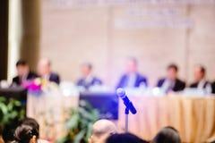 Rozmyty mikrofon z przewodniczącym spotkania i komitetu wykonawczego tło w audytorium dla udziałowów spotyka lub zdjęcia stock