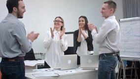 Rozochoceni biurowi ludzie oklaskuje ich ręki i trząść po wielkiej pracy obraz stock