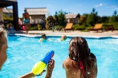 Rozochoceni dzieci bawić się waterguns, cieszenie, doskakiwanie, pływa w basenie obraz stock