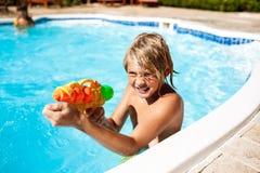 Rozochoceni dzieci bawić się waterguns, cieszenie, doskakiwanie, pływa w basenie zdjęcie royalty free