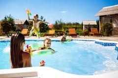 Rozochoceni dzieci bawić się waterguns, cieszenie, doskakiwanie, pływa w basenie zdjęcia royalty free