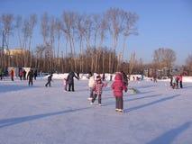 Rozochoceni dzieci jadą w zimy łyżwiarstwie na dużym lodowisku fotografia stock