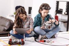 Rozochoceni dzieciaki używa nowożytnych gadżety i przyrząda w domu fotografia stock
